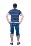 Young man looks at  white background. rear view. Royalty Free Stock Image
