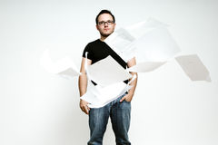 A young man with lots of paperwork. A young man with lots of paperwork being thrown in the air Stock Image