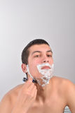 Young man with lots of shaving cream on his face prepar Stock Images