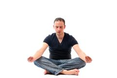 Young man in lotus position exercising yoga Stock Images