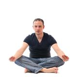 Young man in lotus position exercising yoga Stock Photography