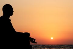 Young man in lotus position & meditating on beach. A young man sitting in lotus position and meditating on a beach in the evening with sun setting in the Royalty Free Stock Image