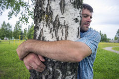 Young man with love hugs birch Stock Image