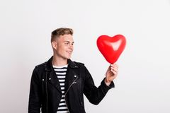 A young man in love standing in a studio, holding a red heart balloon. royalty free stock photography