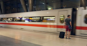 Young man with luggage get onboard to fast ICE train stock video footage