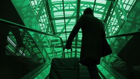 Young man with luggage moves along escalator at airport indoors. Male rises up moving on automatic tape, holding big suitcase with hand then goes ahead. Asian stock footage