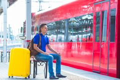 Young man with luggage at a train station waiting Stock Images