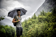 Young man in lush, green mountains holding an umbr Stock Image
