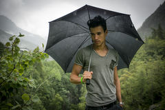 Young man in lush, green mountains holding an umbrella Royalty Free Stock Photo