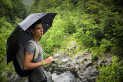 Young man in lush, green mountains holding an umbrella stock image