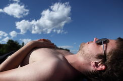 Young man lying on a beach,. Sunbathing under lovely summer sky Stock Photo