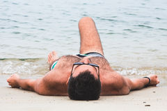 Young man lying on the beach. By the water Stock Images