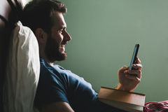 Young man lying in the bed with a book  and a smartphone Stock Photo