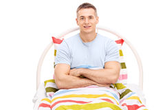 Young man lying in bed covered with a blanket Royalty Free Stock Photography