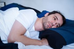 Portrait of sad man lying in the bed and trying to sleep in the morning. Young man lying in the bed feeling bad and trying to sleep in the morning Stock Photos