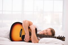 Young man lying in bed with guitar Stock Photography
