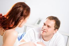 Young man lying in bed with his girlfriend Royalty Free Stock Photo