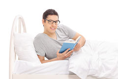 Young man lying in bed and holding a book Stock Images