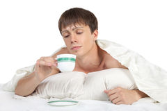 Young, man lying in bed and holding a cup Royalty Free Stock Photography