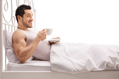 Young man lying in bed and holding a cup Stock Photo