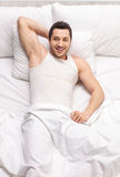 Young man lying in bed Royalty Free Stock Image