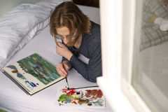 Young man lying in bed painting a picture Royalty Free Stock Images