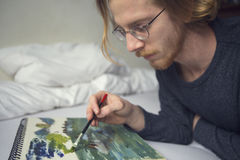 Young man lying in bed painting a picture Royalty Free Stock Photos
