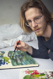 Young man lying in bed painting a picture Royalty Free Stock Photo