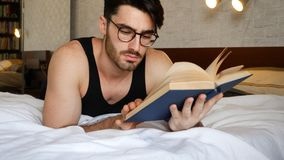 Young man lying in bed and reading a book. Young handsome man lying in bed and reading a book in his bedroom at home Stock Photos