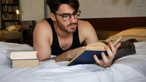 Young man lying in bed and reading a book. Young handsome man lying in bed and reading a book in his bedroom at home Stock Photo