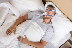 Man With Sleeping Apnea And CPAP Machine. Young Man Lying On Bed With Sleeping Apnea And CPAP Machine stock images
