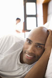 Young man lying in bed, smiling, portrait, woman in background Royalty Free Stock Photography