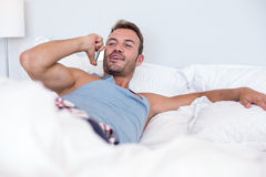 Young man lying on bed Stock Images