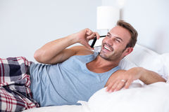 Young man lying on bed Stock Photos