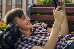 Young man lying on bench in park and readindg Stock Photography