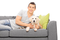 Young man lying on couch with a puppy Stock Photography