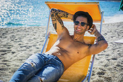 Young man lying on deckchair at beach Stock Photos