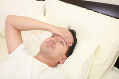 Young man lying down in bed Stock Image