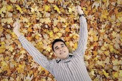 Young man lying down on the leaves autumn Stock Image