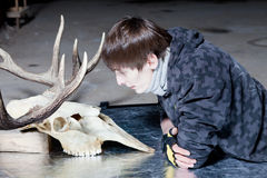 Young man lying down looking at the deer skull Stock Photography