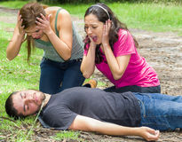 Young man lying down with medical emergency, two young women acting hysterically, outdoors environment Royalty Free Stock Images