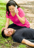 Young man lying down with medical emergency, woman sitting by his side calling for help, outdoors environment Stock Photography