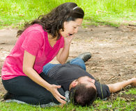 Young man lying down with medical emergency, woman sitting by his side calling for help, outdoors environment Royalty Free Stock Photo