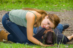 Young man lying down with medical emergency, woman sitting by his side checking for breath, outdoors environment Royalty Free Stock Image