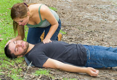 Young man lying down with medical emergency, young woman sitting by his side performing light treatment, outdoors Stock Image