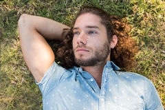 Young man lying down in the park Stock Image