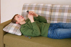 Young man lying down on the sofa, sending text message Royalty Free Stock Image
