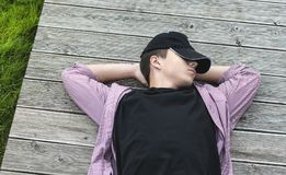 Young man has a rest lying on the boards Royalty Free Stock Photo