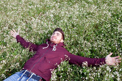 Young man lying on a field of flowers Royalty Free Stock Image