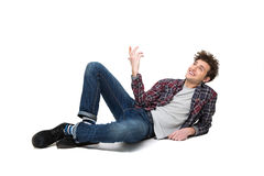 Young man lying on the floor and looking up. Happy thoughtful young man lying on the floor and looking up at copyspace Stock Image